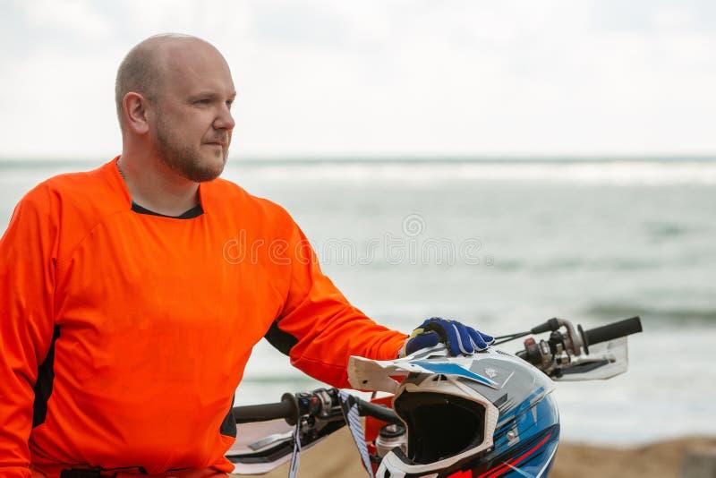 Il motociclista in un vestito protettivo sta accanto alla motocicletta davanti al mare fotografie stock