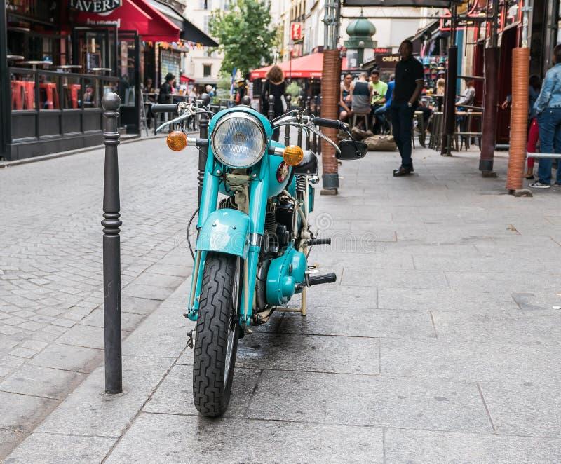 Il motorino di motore blu di Teal ha parcheggiato sul marciapiede di Parigi immagini stock libere da diritti