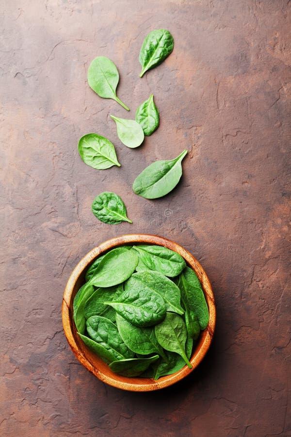 Il mucchio degli spinaci del bambino lascia in ciotola di legno sulla vista rustica del piano d'appoggio Alimento organico di die fotografia stock