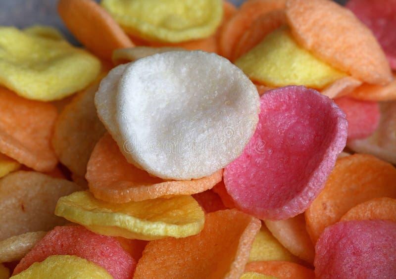 Il mucchio dei chip multicolori del gamberetto si chiude su fotografia stock