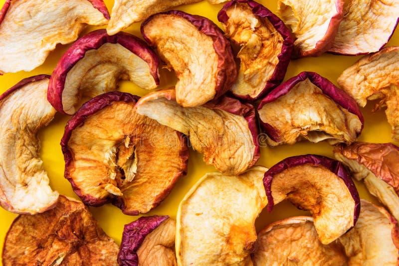 Il mucchio dei frutti seccati al sole organici ha disidratato le mele sparse su fondo giallo luminoso Wholefoods di dieta sana immagine stock