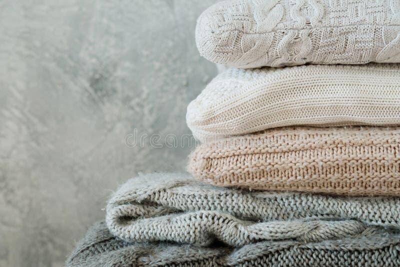Il mucchio ha piegato la decorazione domestica tricottata accogliente dei cuscini dei plaid fotografia stock libera da diritti