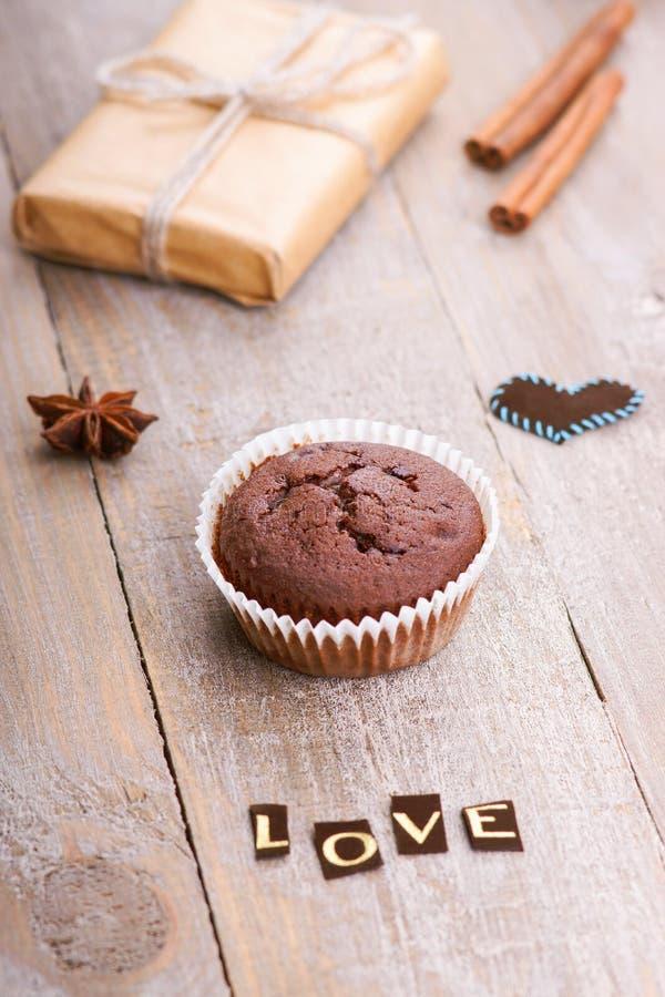 Il muffin del cioccolato, il contenitore di regalo e la parola amano immagini stock libere da diritti