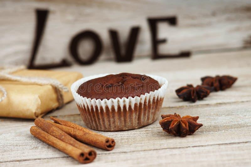 Il muffin del cioccolato, il contenitore di regalo e la parola amano fotografia stock