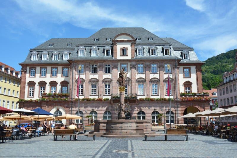 Il municipio della città al mercato con la fontana e statua davanti e la gente che si siede dentro si battono fotografia stock