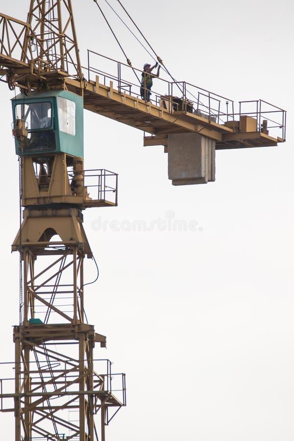 Il muratore assiste a manutenzione su una gru a torre fotografia stock