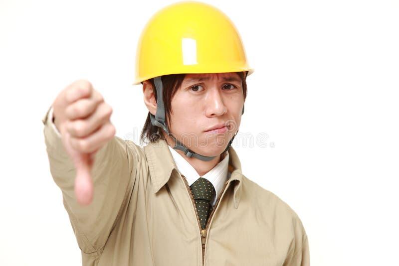 Il muratore di Apanese con i pollici giù gesture fotografia stock