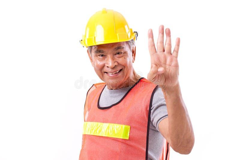 Il muratore felice e sorridente che indica su 4 dita gesture fotografie stock libere da diritti