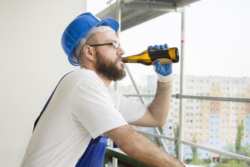 Il muratore nell'usura del lavoro, in guanti protettivi ed in un casco sulla testa beve la birra dalla bottiglia Lavoro ad elevat fotografia stock