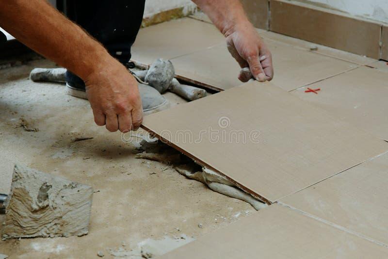 Il muratore ? pavimento non tappezzato a casa Ponendo le mattonelle sul pavimento fotografie stock libere da diritti