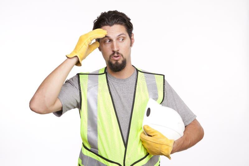 Il muratore pulisce il sudore della sua fronte in un gesto fotografia stock libera da diritti
