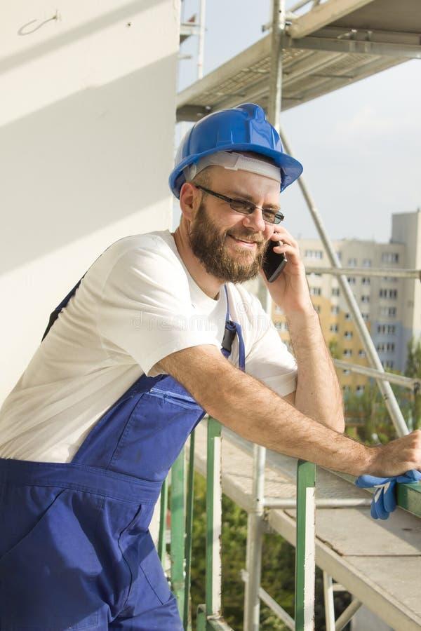 Il muratore sorridente nel lavoro equipaggia e casco sulla testa che parla sul telefono Lavoro ad elevata altitudine immagini stock libere da diritti