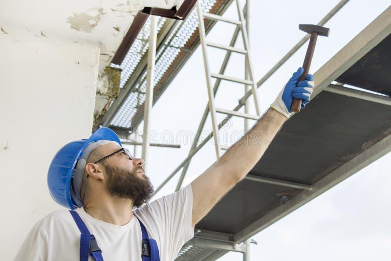 Il muratore in un abbigliamento del lavoro, nei guanti protettivi ed in un casco sulla testa dà un martello Lavoro ad elevata alt fotografia stock