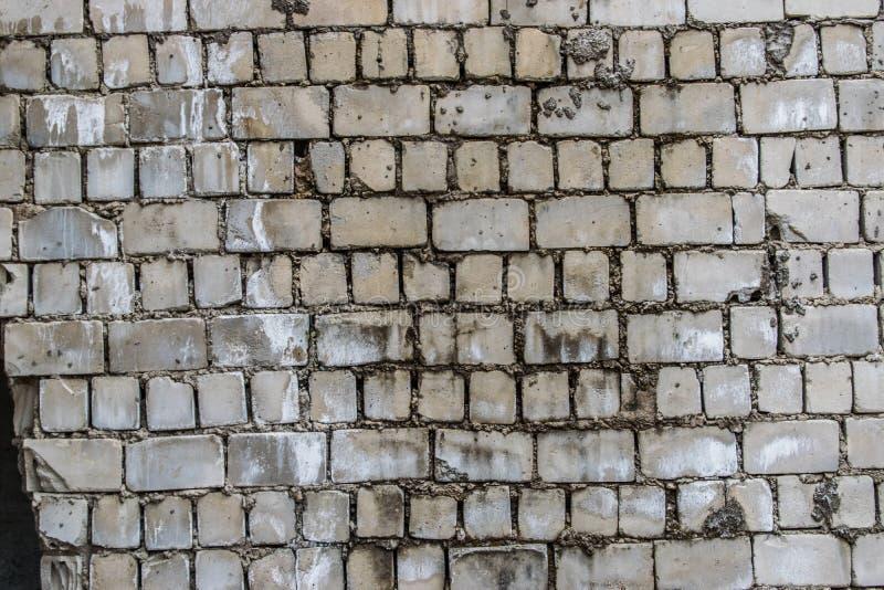 Il muro di cemento del fondo, tracce di alterazione causata dagli agenti atmosferici, parete indossata ha danneggiato la vecchia  immagine stock