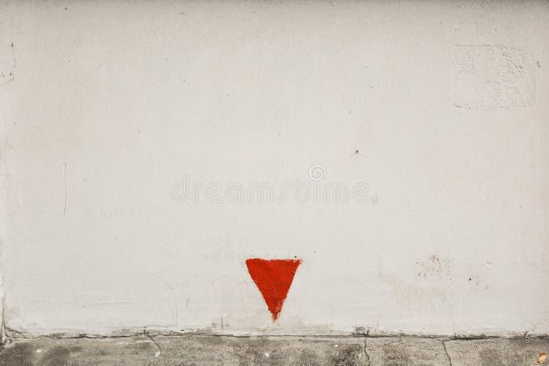 Il muro di cemento ruvido bianco con con la freccia rossa ha girato il basso superiore fotografie stock