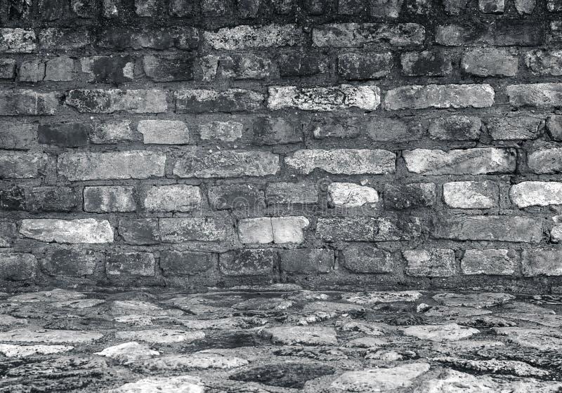 Il muro di mattoni e la pietra Grungy pavimentano la stanza come fondo fotografia stock