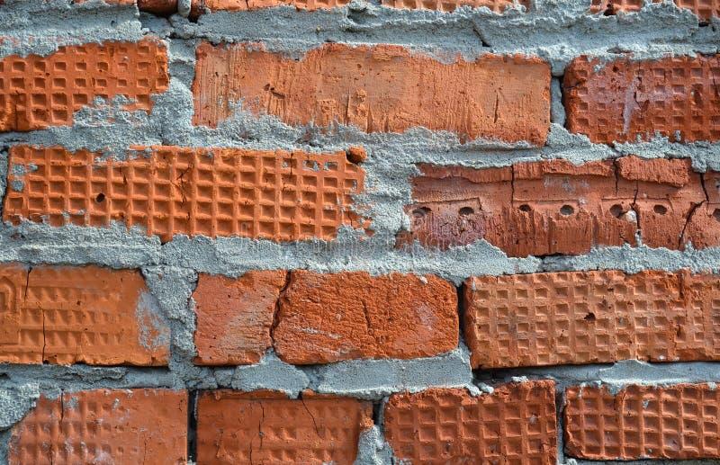 Il muro di mattoni rosso è composto di mattoni differenti nella struttura fotografie stock