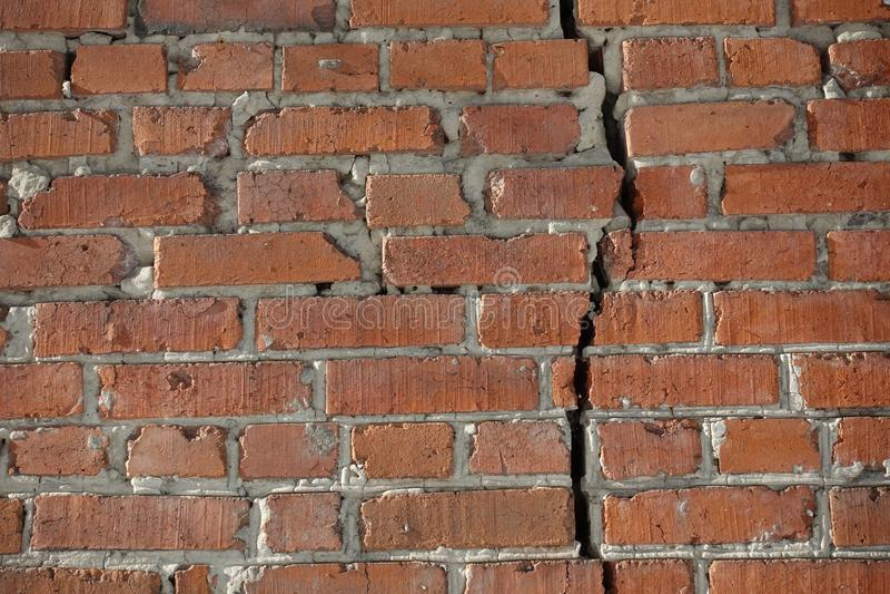 Il muro di mattoni rosso è diviso da una crepa verticale Concetto di separazione immagini stock libere da diritti