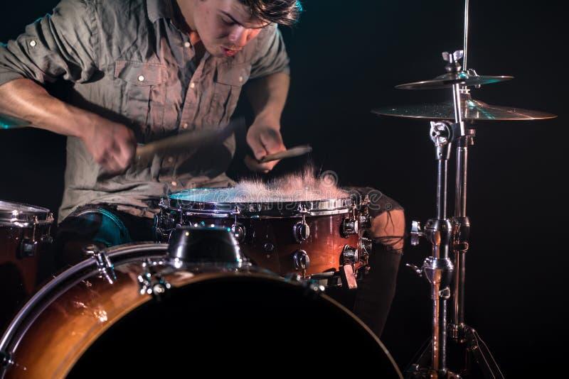 Il musicista che gioca i tamburi con spruzza, fondo nero con bella luce morbida fotografie stock libere da diritti