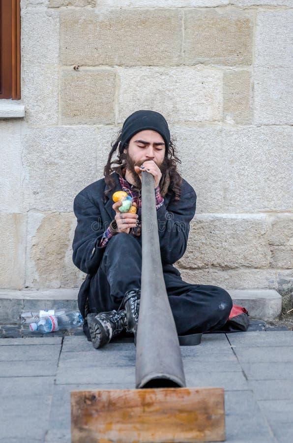 Il musicista della via con capelli lunghi e una barba gioca la musica lunga del tubo che pende indietro contro la parete della ca fotografie stock