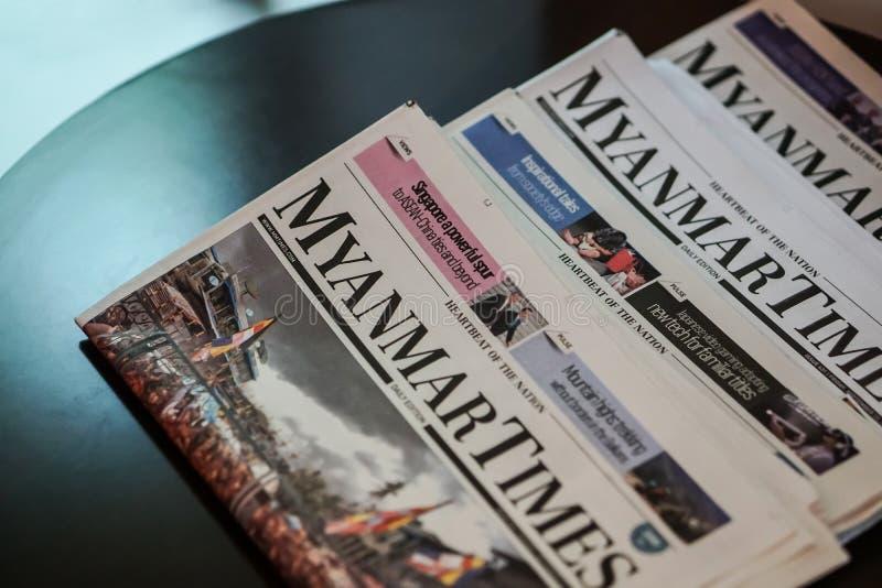 Il Myanmar cronometra il giornale sulla tavola in un hotel fotografie stock