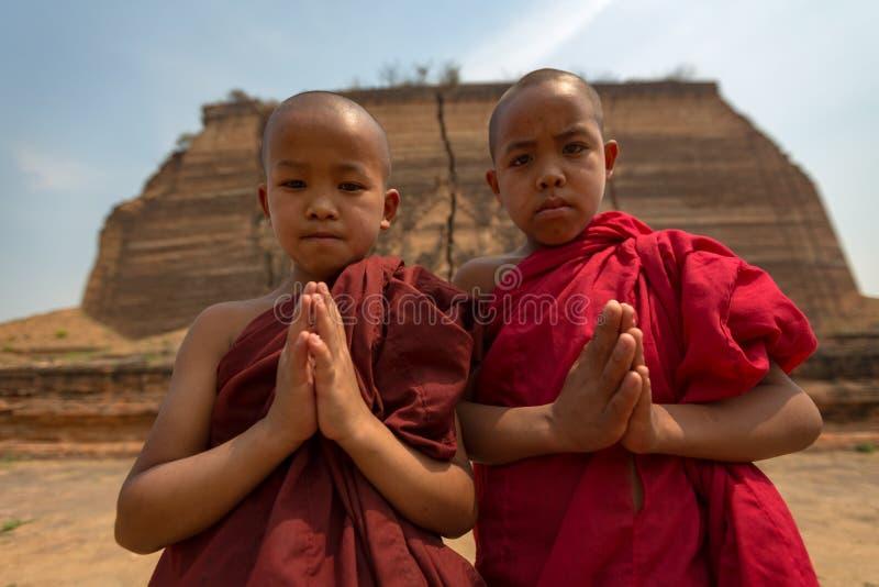 Il Myanmar due piccoli monaci paga la fede di rispetto di buddismo in Myan immagine stock