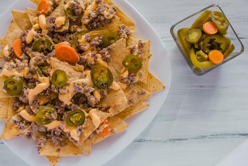 Il nacho scheggia il cereale guarnito con carne tritata, formaggio fuso, alimento piccante messicano dei peperoni dei jalapeni ne immagine stock