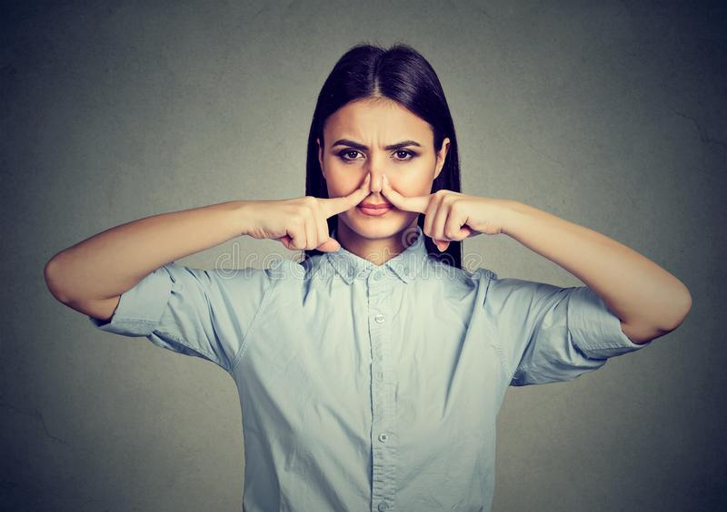 Il naso di pizzichi della donna con gli sguardi delle dita con repulsione qualcosa puzza il cattivo odore fotografia stock
