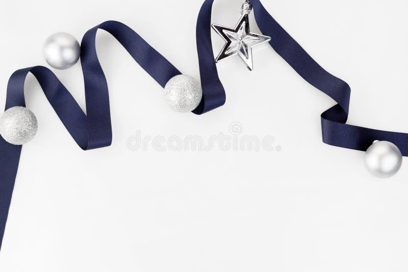 Il nastro blu di Natale decora con le palle e la stella d'argento dell'ornamento di scintillio su fondo bianco immagini stock