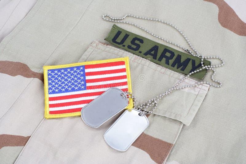 Il nastro del ramo dell'ESERCITO AMERICANO con le medagliette per cani e la toppa della bandiera sul cammuffamento del deserto un immagini stock libere da diritti