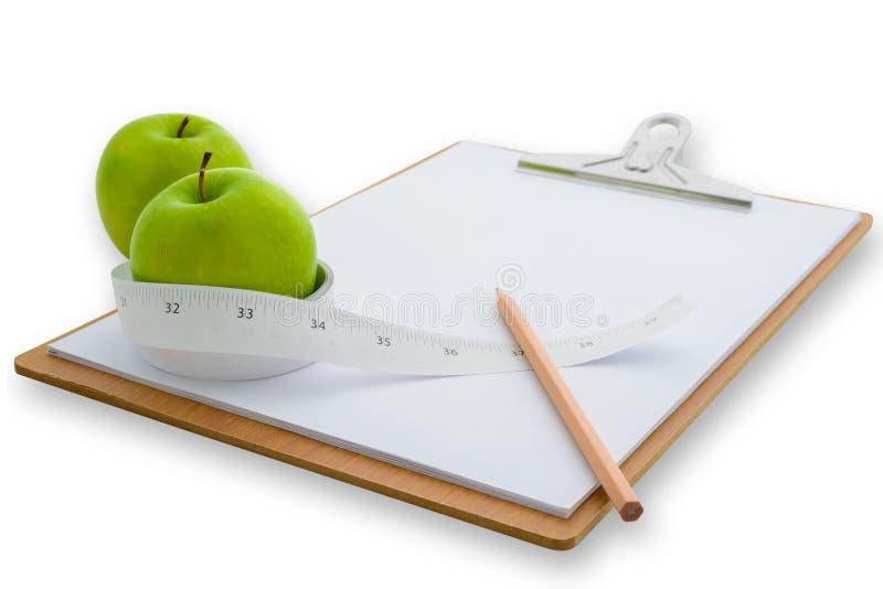 Il nastro di misurazione ha avvolto una mela e una lavagna per appunti verdi immagini stock libere da diritti