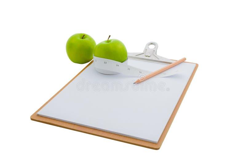 Il nastro di misurazione ha avvolto una mela e una lavagna per appunti verdi fotografia stock