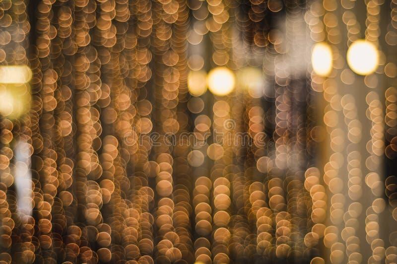 Il Natale confuso dorato incatena le luci che creano un bello bokeh fotografia stock