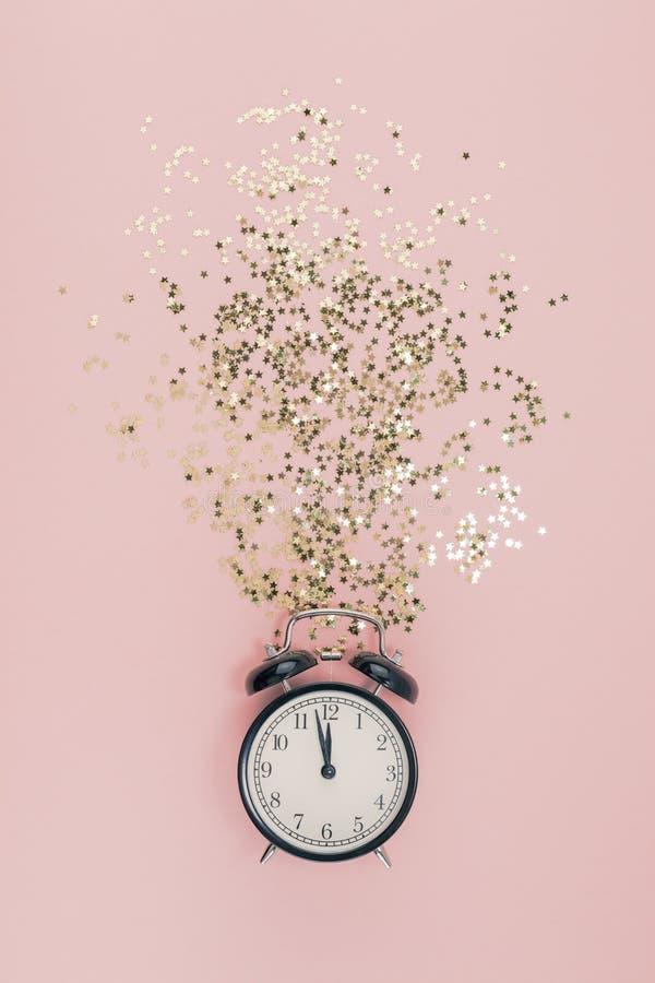 Il Natale del nuovo anno la vista di cima che pone pianamente la sveglia nera dodici ha coperto la carta rosa millenaria di color fotografia stock libera da diritti