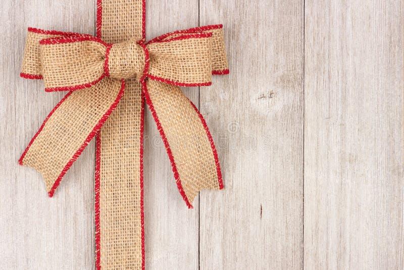 Il Natale della tela da imballaggio si piega ed il lato del nastro rasenta il vecchio legno bianco fotografie stock