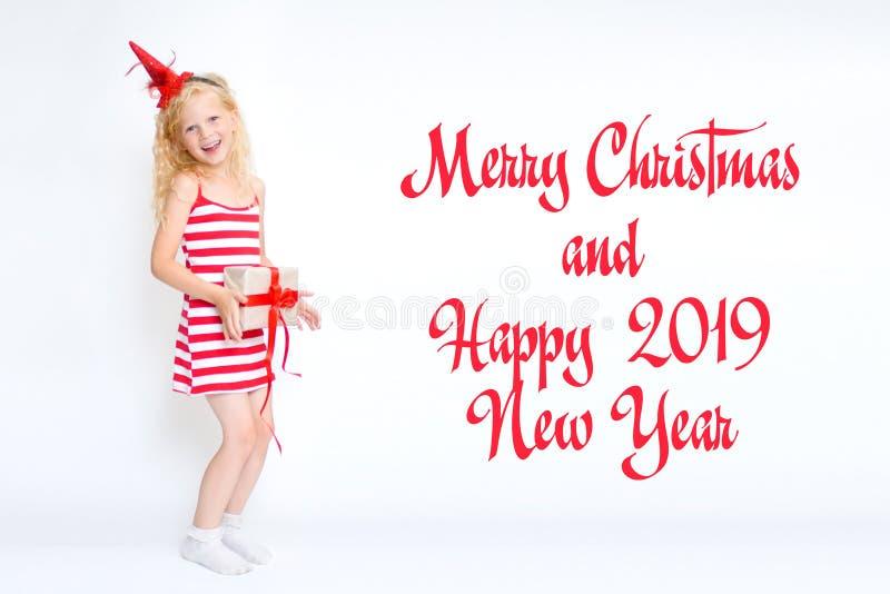 Il Natale ed il nuovo anno cardano 2019 con la piccola ragazza bionda sveglia felice in vestito rosso e bianco dal costume di car fotografia stock libera da diritti
