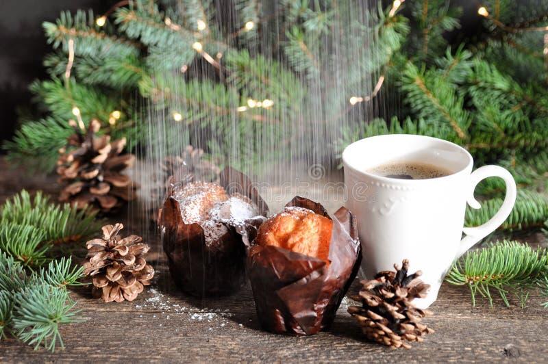 Il Natale fa colazione di due bigné e di una tazza di caffè caldo spruzzata con lo zucchero in polvere, sui precedenti dei rami d fotografia stock libera da diritti