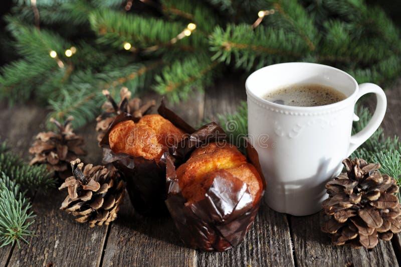 Il Natale fa colazione di due bigné e di una tazza di caffè caldo su una tavola di legno, sui precedenti dei rami dell'abete con  fotografia stock