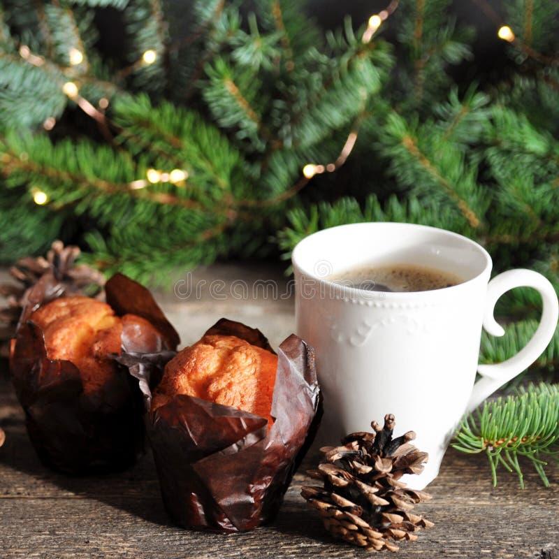 Il Natale fa colazione di due bigné e di una tazza di caffè caldo su una tavola di legno, sui precedenti dei rami dell'abete con  fotografia stock libera da diritti
