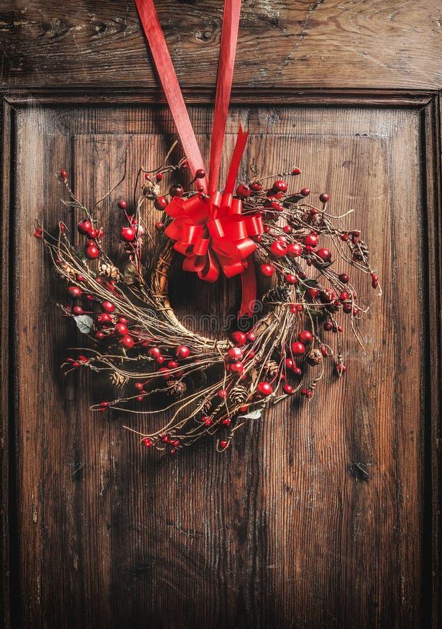 Il Natale fatto a mano avvolge l'attaccatura sulla porta di legno con il nastro e le bacche rossi fotografie stock libere da diritti