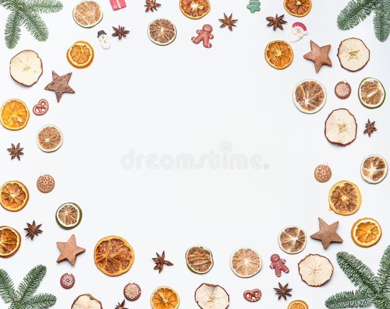 Il Natale incornicia fatto con i rami dell'abete e frutti, spezie e caramelle secchi di festa sul fondo bianco dello scrittorio D immagine stock libera da diritti