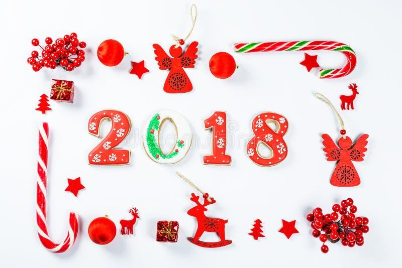 Il Natale incornicia fatto dei giocattoli e delle decorazioni rossi del nuovo anno con i biscotti 2018 del pan di zenzero immagine stock