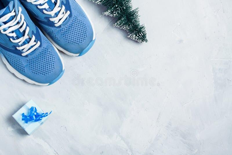 Il Natale mette in mostra la composizione con le scarpe ed il contenitore di regalo blu immagine stock