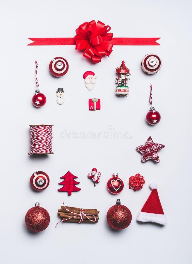 Il Natale orna la composizione nella struttura di disposizione del piano su fondo bianco, vista superiore Spostamento rosso della fotografie stock