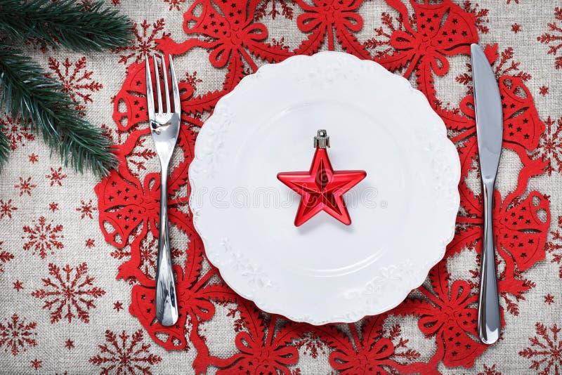 Il Natale placca sul fondo di festa con la stella rossa fotografia stock