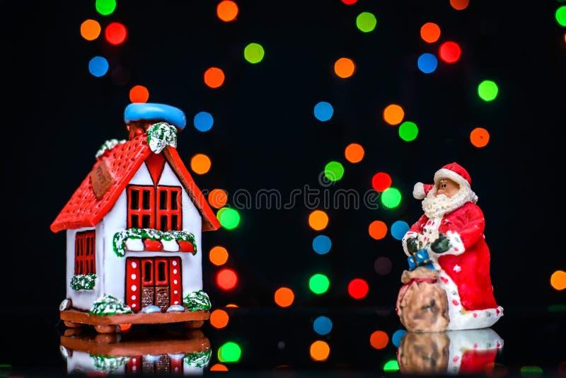 Il Natale rappresenta con Santa e la casa su un fondo delle luci colorate immagine stock