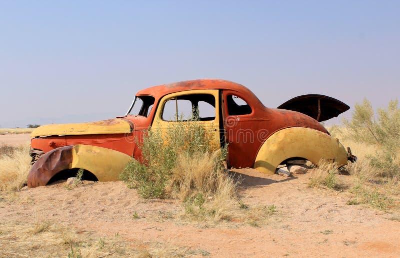 Il naufragio arrugginito dell'automobile in fine dispone nel deserto di Namib immagini stock libere da diritti