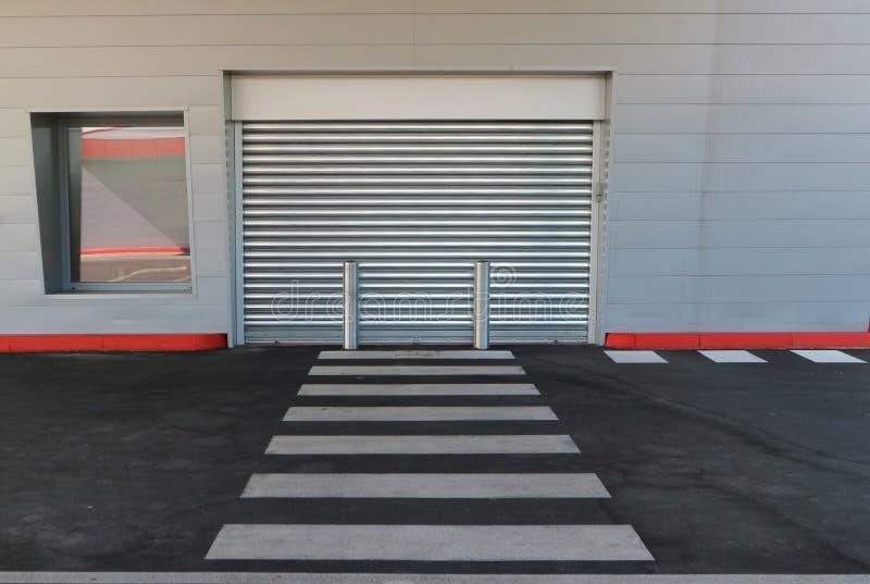 Il negozio chiuso con il portone del metallo ha tirato giù È in una costruzione moderna fatta di rivestimento di alluminio, con u immagini stock