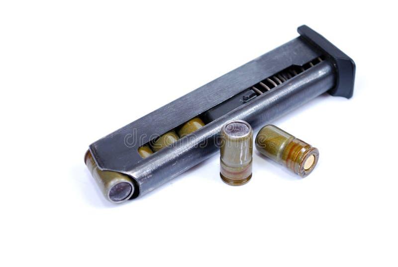 Il negozio ha caricato con quattro cartucce traumatiche da una bugia della pistola del fuoco e di 2 capi vicino fotografia stock