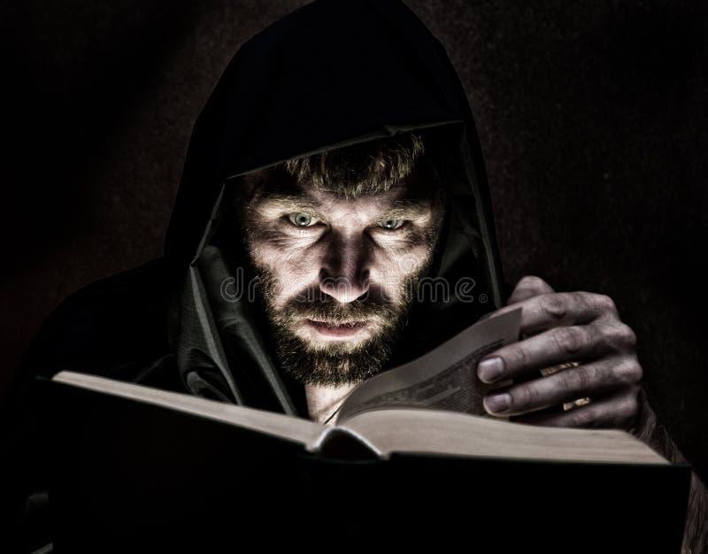 Il negromante lancia gli incantesimi dal libro antico spesso da lume di candela su un fondo scuro immagini stock